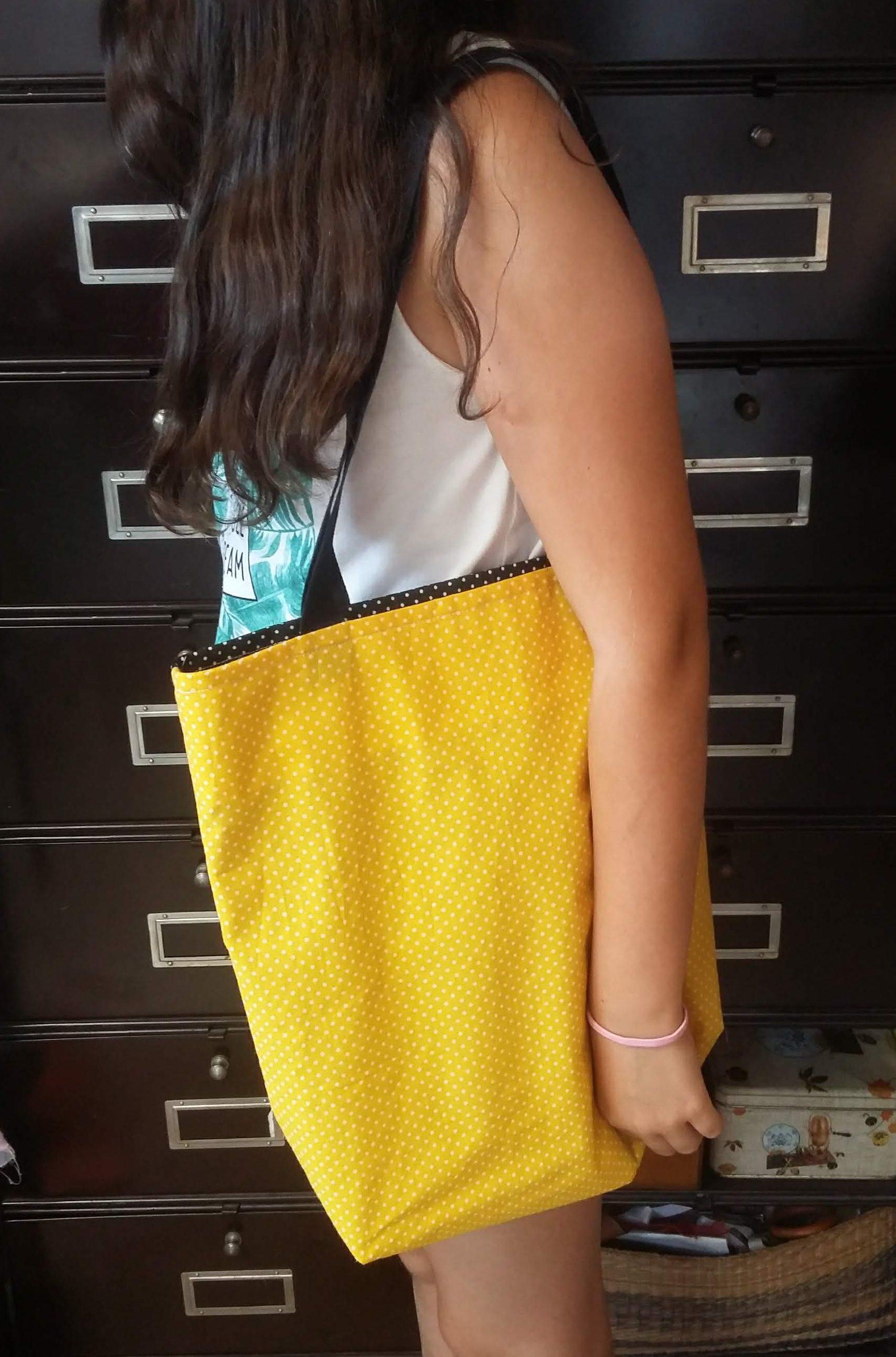 Sac ou tote bag bicolore en tissu coton noir à pois blanc et en tissu coton jaune à pois blanc avec des sangles noires en coton, réalisé par une élève débutante lors d'un cours de couture de deux heures